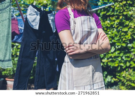 A young woman wearing an apron is standing by her laundry drying on a clothes line in the garden