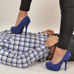 A young woman wearing elegant pumps, dominating in an authoritative manner a man lying down submissively, by stomping him on the chest.