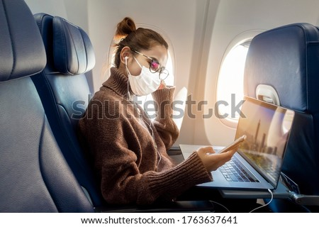 A young woman wearing face mask is traveling on airplane , New normal travel after covid-19 pandemic concept  Stockfoto ©