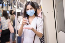 A young woman wearing protective mask in subway is using alcohol to wash hands, travel under Covid-19 pandemic, safety travels, social distancing protocol, New normal travel concept