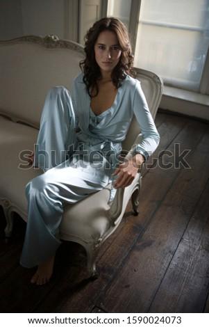 A young woman wearing silk pyjamas