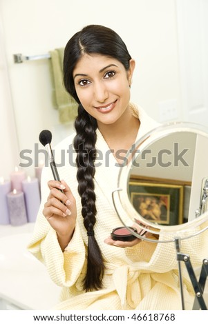 A young woman wears a bathrobe while holding a makeup brush and smiling at the camera. Her long dark hair is braided and hanging over her shoulder. Vertical shot.