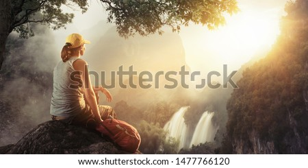 A young woman with a backpack on top of a hill in silence and loneliness is resting in the mountains admiring a beautiful waterfall at sunset.