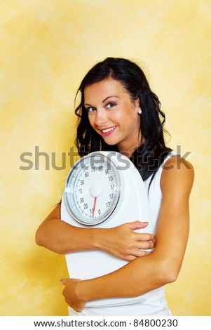a young woman with a balance in his hand smiling after a successful diet