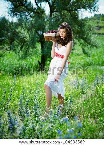 A young woman with a basket of cherries in the hands of