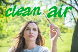 A young woman with a brush paining Clean air message (green)