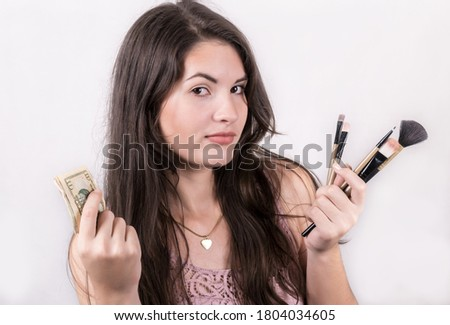 A young woman with a funny expression on her face while holding make up brushes in one hand and dollar bills on the other. ストックフォト ©
