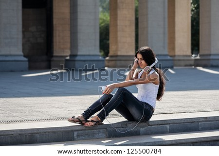 A young woman with a headphones sitting on the stairs, near the