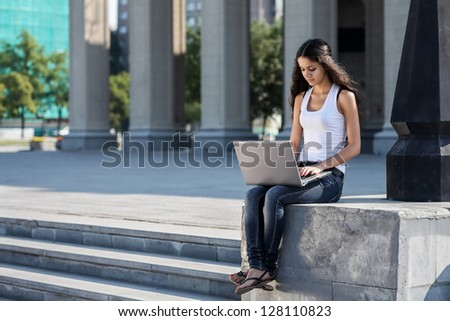 A young woman with a laptop sitting on the stairs, near the university