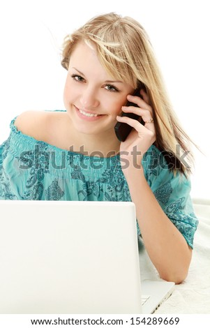 A young woman with a laptop talking on the phone