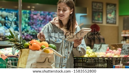 A young woman with a notebook buys groceries in the supermarket. Health food. Healthy food, organic food.
