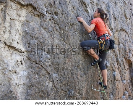 A young woman with a rope engaged in the sports of rock climbing on the rock. #288699440
