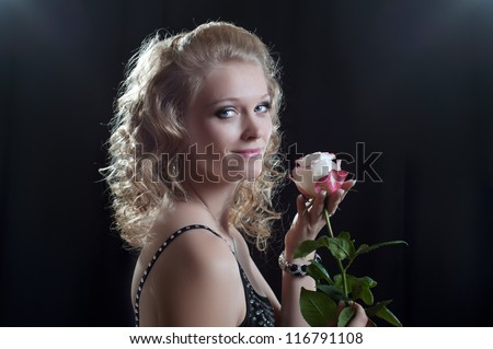 A young woman with a rose,  black background