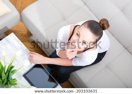 A young woman with a tablet pc on the sofa. #203103631