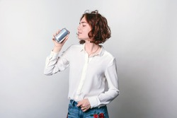 A young woman with a tin can, a metal soda can, or a beer can in front. cylindrical aluminum cans, bottles of cold drinks, a woman holding a metal can.