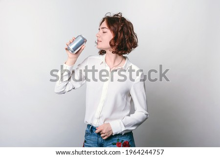A young woman with a tin can, a metal soda can, or a beer can in front. cylindrical aluminum cans, bottles of cold drinks, a woman holding a metal can. Stock photo ©