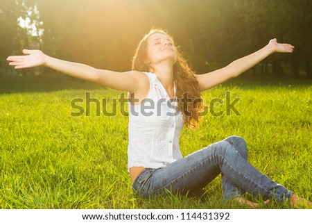 A young woman with arms outstretched in the sun