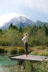 A young woman with blonde hair is meditating in a standing position in calm and relaxing atmosphere at a mountain lake. Yoga girl.