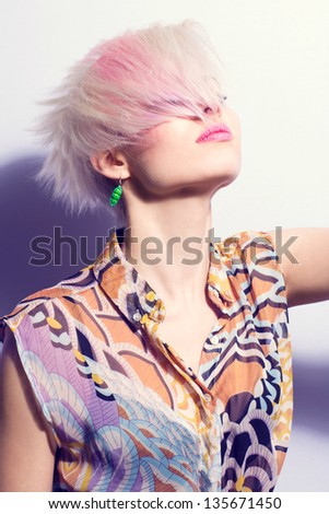 A young woman with creative hair style and 1980s look. Hard light in color.