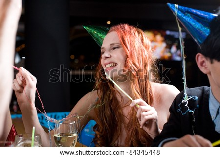 A young woman with long red hair amidst a celebration, wearing a party hat and covered with streamers.