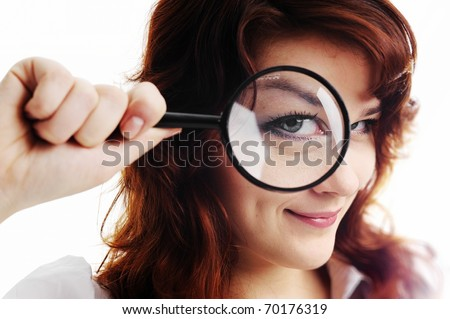 A young woman with magnifying glass at her eye