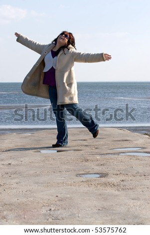 A young woman with red highlights dancing on the jetty at the beach.