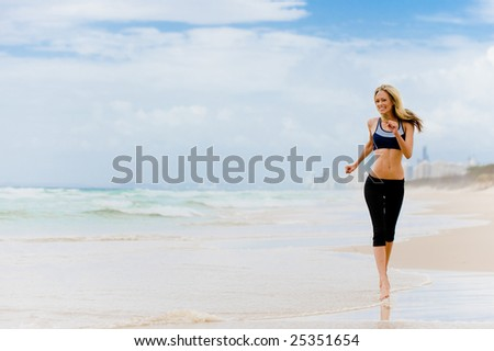 A young woman with running along Surfers Paradise beach in Australia