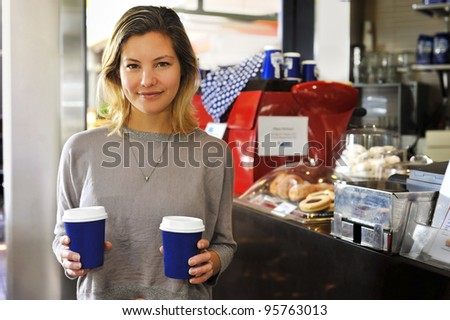 "a young woman with takeaway coffees. This model has a lovely natural ""everyday"" look."