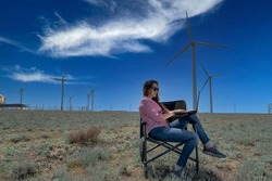 A young woman works at a laptop, sitting in a chair against the backdrop of wind turbines away from people. The concept of freedom to choose a place of work. Modern technology.