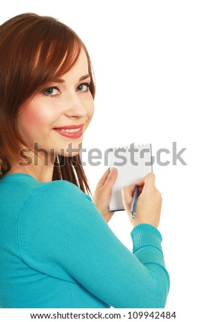 A young woman writing in a notebook isolated on a white background.