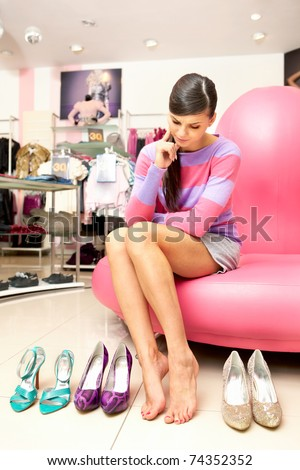 A young women sitting in shop and thinking what shoes to buy - stock photo