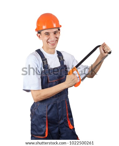 A young worker in a helmet holds a hacksaw and smiles into the camera. Image for advertising works on repair and construction.