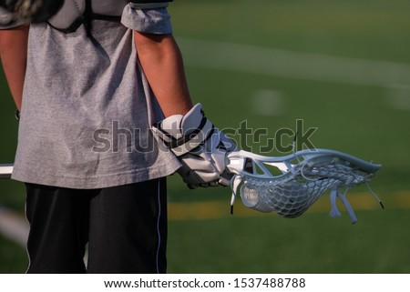 A youth lacrosse player holding a men's lacrosse stick on a lacrosse field.