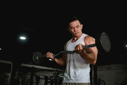 A youthful and muscular asian man in a white tank top does some barbell curls at the gym. An active 40 year old with healthy lifestyle.