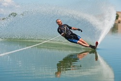 A 50 yr. old man slalom waterskiing on Sweitzer Lake in Delta, Colorado. He is carving the water with his ski as he makes a turn, creating a