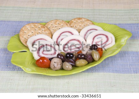 A yummy snack plate of prosciutto ham basil cheese rolls with an olive assortment and crackers.
