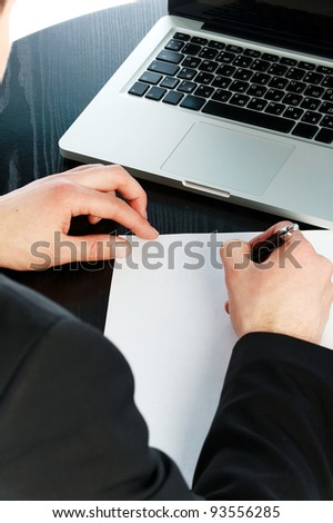 A yuong business man writing in a paper
