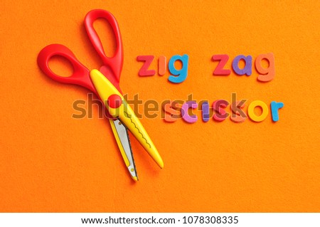 A zigzag scissor with the words zigzag scissor on an orange background #1078308335