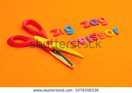 A zigzag scissor with the words zigzag scissor on an orange background #1078308338