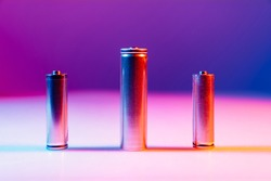 AA and 8650 Li-ion silver batteries on illuminated by multicolored light background. disposable batteries and accumulators.
