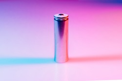 AA silver battery on illuminated by multicolored light background. disposable batteries and accumulators. reusable