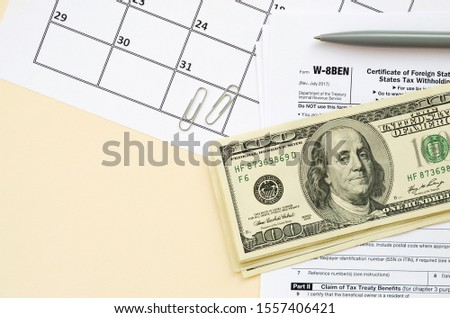 aaaaaForm W-8BEN Certificate of foreign status of beneficial owner for United States tax withholding and reporting for individuals blank lies with pen and hundred dollar bills on calendar page #1557406421