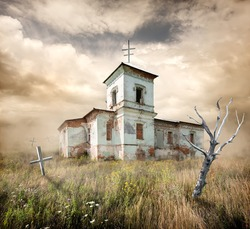 aAbandoned church near the cemetery in a field