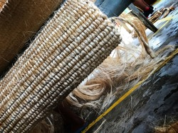 Abaca woven mats rolled with abaca fibers in the background