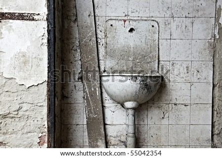 Abandon, ruined basin on dirty, grungy wall - stock photo