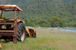 abandoned agriculture tractor in an overgrown field of a bankrupt farmer