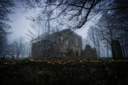 Abandoned and decayed church on a misty day