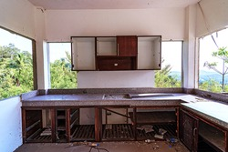 Abandoned and destroyed house in the jungle forest. Destroyed kitchen with the palm tree forest view. Thailand hotel destroyed and without people.