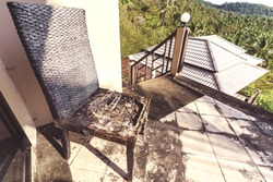 Abandoned and destroyed house in the jungle forest. View from the destroyed balkony to the jungle. Old destroyed chair. Thailand hotel destroyed and without people.