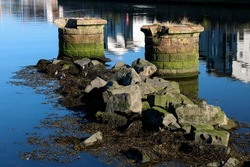Abandoned and dilapidated bridge piers in a river estuary